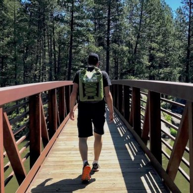 This photo shows the ICEMULE Pro cooler being worn by a hiker on a bridge outside near trees and a lake.