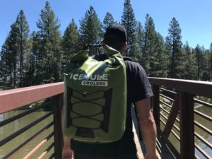 This photo shows the author wearing an ICEMULE Pro soft-sided backpack cooler while crossing a footbridge outdoors.