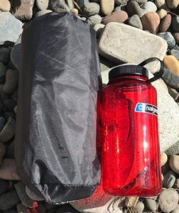 This photo shows the Therm-a-Rest NeoAir XLite sleeping pad packed in its stuff sack next to a Nalgene water bottle.