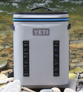 This photo shows the front of the YETI Hopper Backflip 24 outside near a river.