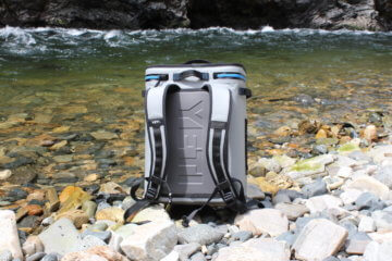 This photo shows the YETI Hopper BackFlip 24 backpack cooler on the side of a river.