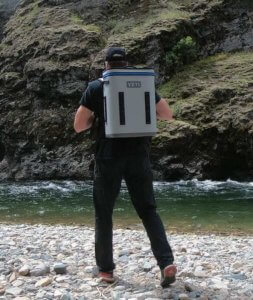 This photo shows a man wearing the YETI Hopper Backflip 24 backpack cooler near a river.