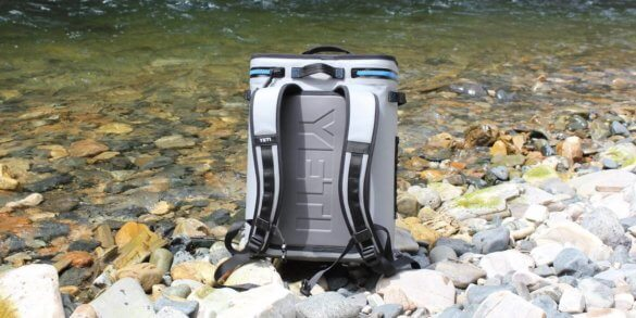This photo shows the YETI Hopper Backflip 24 backpack cooler on rocks by a river.