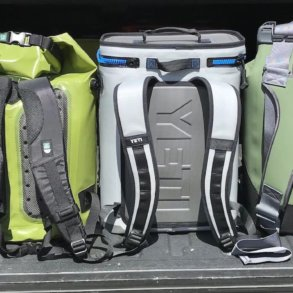 This photo shows several backpack coolers in a row, including the YETI Hopper BackFlip 24, OtterBox Trooper LT 30, and ICEMULE Pro.
