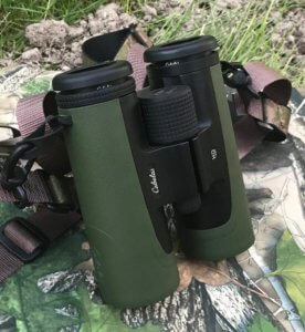 This review photo shows the Cabela's Instinct 10x42 HD binoculars on a camo and grass background outside.