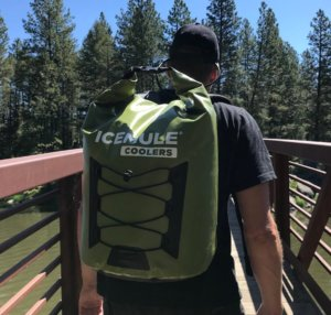 This photo shows a man wearing an ICEMULE Pro backpack cooler walking across a bridge.