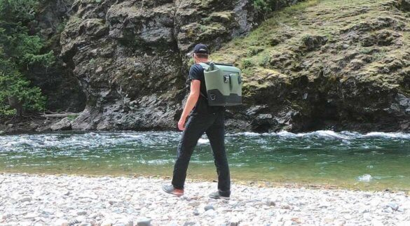 This photo shows a man carrying the OtterBox Trooper LT 30 backpack cooler near a river.