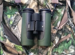This photo shows the Cabela's Instinct HD 10x42 Binoculars hanging from a Cabela's Hybrid Binocular Harness.