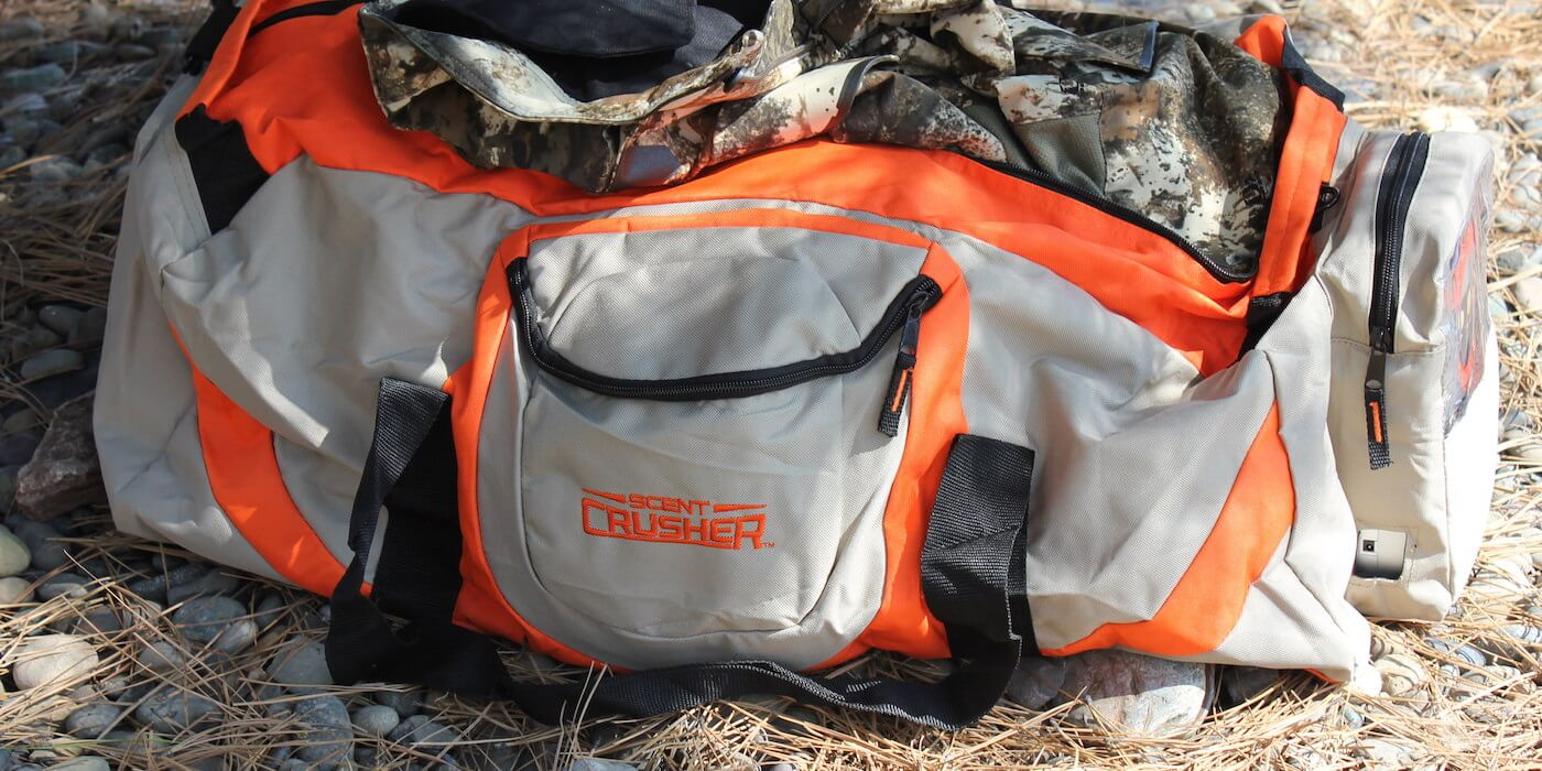 This Scent Crusher Ozone Gear Bag review photo shows the Ozone Gear Bag with some camo hunting clothes.
