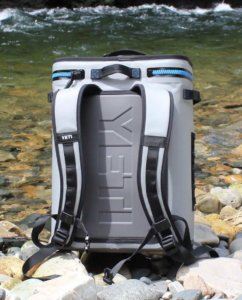This photo shows the YETI Hopper BackFlip 24 backpack cooler outside on rocks near a river.