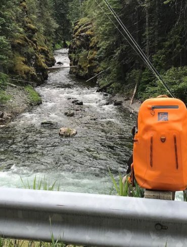 This photo shows a waterproof fishing backpack near a river and stream.