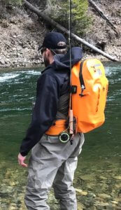 This photo shows a waterproof fishing backpack being worn by a fisherman near a river.