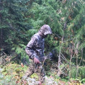 This photo shows the Cabela's Space Rain Jacket being worn by a hunter in the forest.