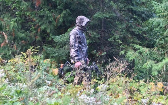 This photo shows the Cabela's Space Rain Jacket being worn in the woods by a bow hunter.