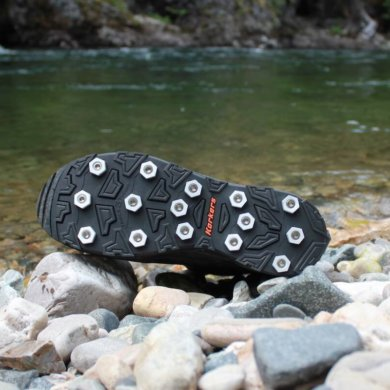 This photo shows the Korkers Triple Threat Aluminum Hex Disc Soles next to a river.