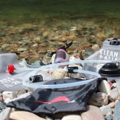 This photo shows the MSR Trail Base Water Filter Kit near a river.