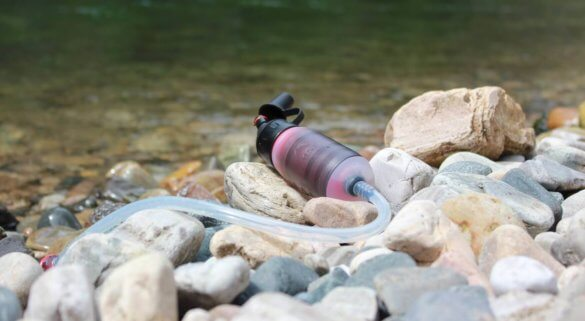 This photo shows the MSR TrailShot water filter on some rocks near a river.