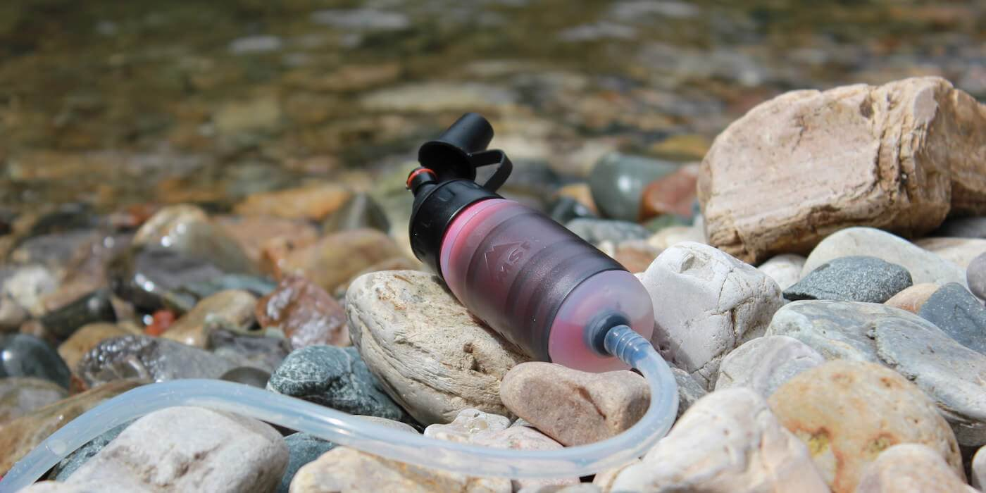 This photo shows the MSR TrailShot water filter near a river.