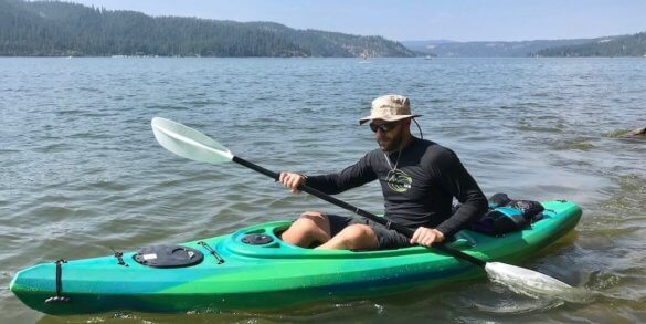 This photo shows the author wearing the Shelta Seahawk hat in a kayak on a lake from the front view.