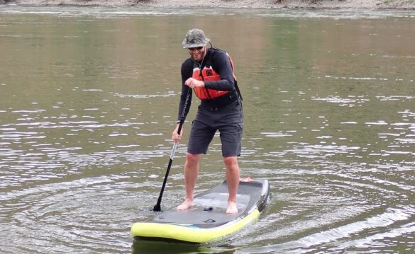 This Shelta Hat review photo shows a man wearing the Shelta Raptor V2 hat while paddle boarding on a river.