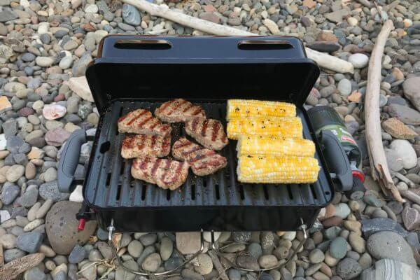 This photo shows the Weber Go-Anywhere Gas Grill with steak and corn on the cob grilling.