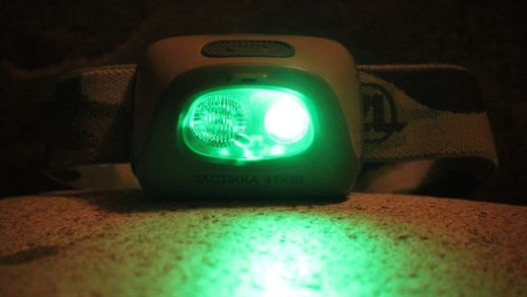 This photo shows a headlamp for hunting with a green light mode enabled in the dark.