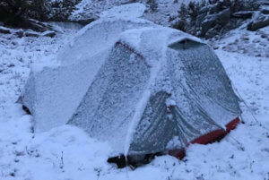 This photo shows a backpacking tent covered in snow where the Therm-a-Rest Parsec 20 sleeping bag was tested.
