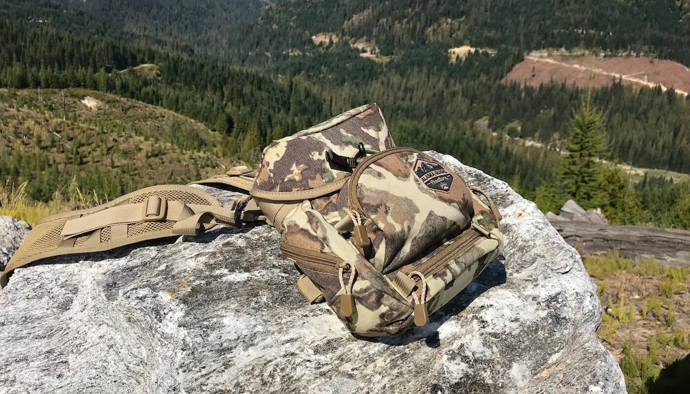 This photo shows the Alaska Guide Creations Classic MAX Pack Bino Harness on a rock outside by a forest.
