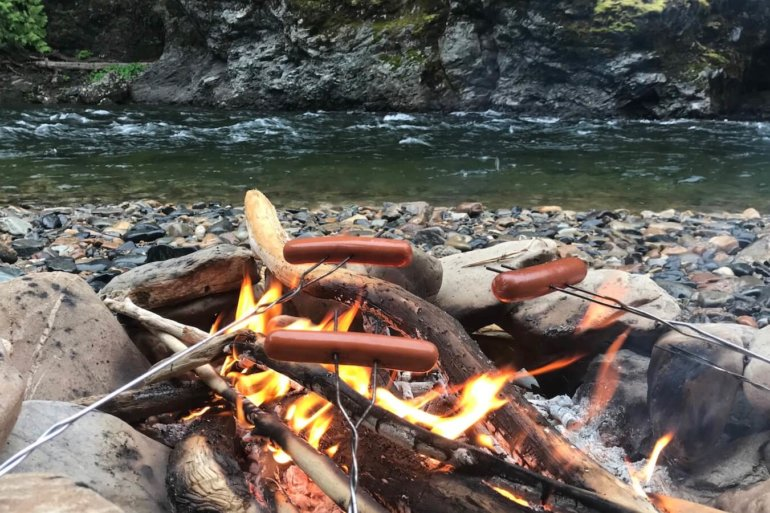 This best camping gear photo shows a campfire with hot dogs roasting over it.