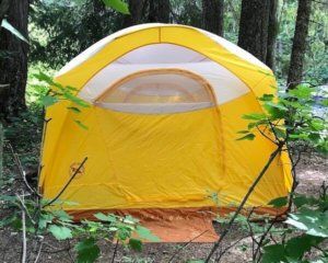 This best camping gifts photo shows the Big Agnes Big House 6 Deluxe Tent in a campsite in a forest.