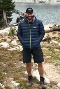 This photo shows a man wearing the Feathered Friends Eos Down Jacket near a mountain lake.