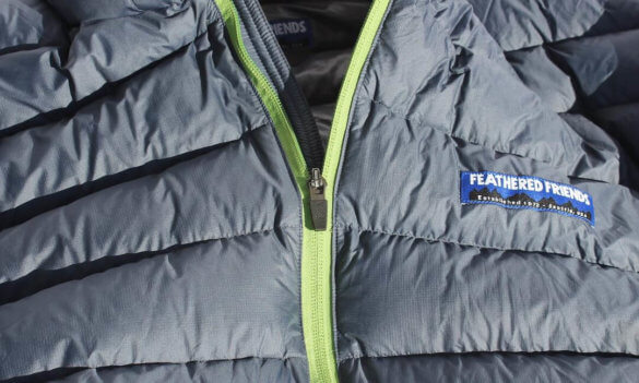 This photo shows the Feathered Friends Eos Down Jacket zipper and logo on the Feathered Friends Eos Down Jacket.