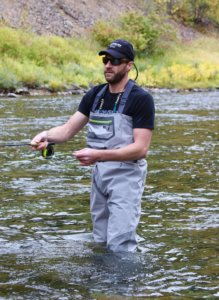 This photo shows a fly fisher wearing the Orvis Ultralight Convertible Waders while fishing on a river.