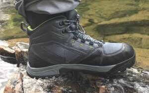 This photo shows the Orvis Ultralight Wading Boots worn with waders from a close-up side view near a river.