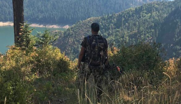 This photo shows a bowhunter standing with a hunting bow overlooking a lake.
