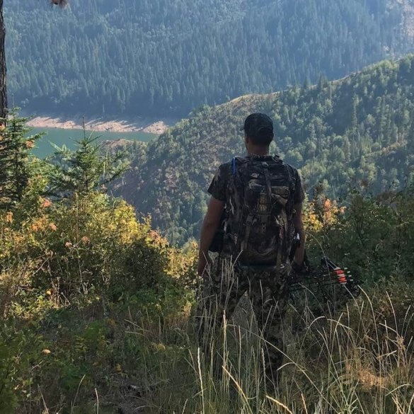 This best bowhunting gift photo shows a bowhunter standing with a hunting bow on a ridge overlooking a lake.