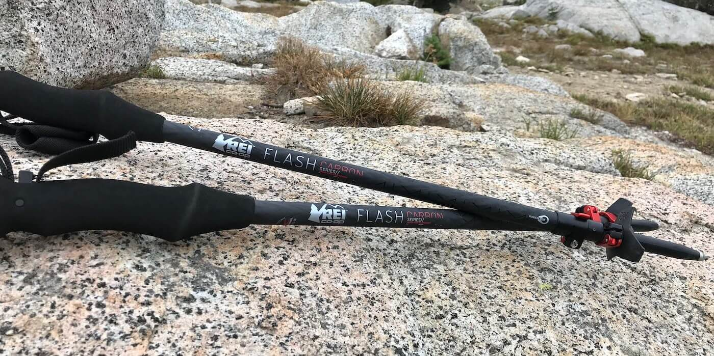 This photo shows the The REI Co-op Flash Carbon Trekking Poles on a rock outside.