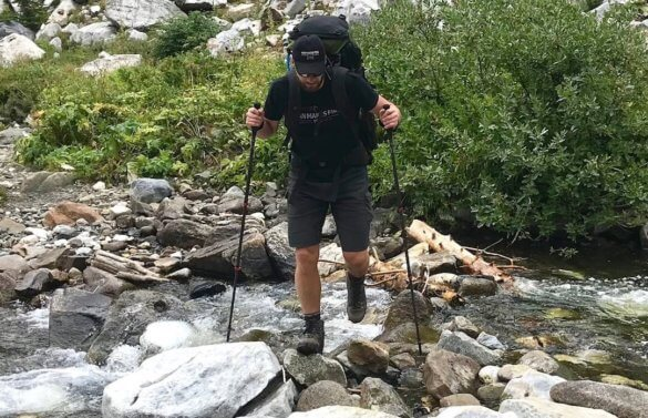 This photo shows the author using the The REI Co-op Flash Carbon Trekking Poles while crossing a stream while backpacking.