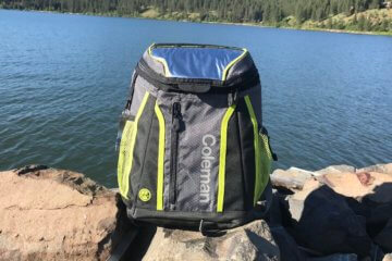 This image shows the Coleman Maverick Ultra Backpack Cooler near a lake.