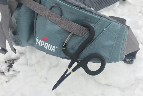 This photo shows the Loon Outdoors Rogue Quickdraw Forceps clipped to a waterproof waist pack for fishing.