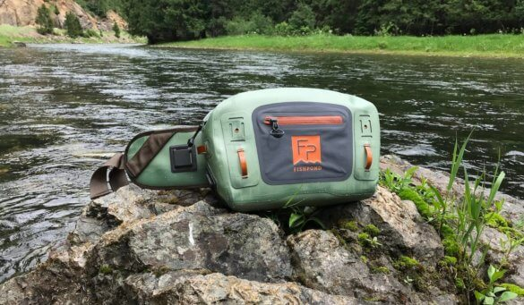 This photo shows the Fishpond Thunderhead Submersible Lumbar Pack on a rock near a river.