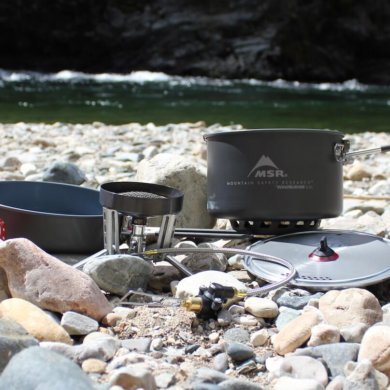 This photo shows the MSR WindBurner Stove System Combo outside near a mountain river.