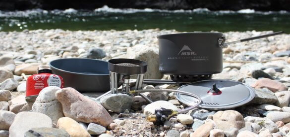 This photo shows the MSR WindBurner Stove System Combo on a rocky shore near a river.
