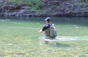 This image shows a fly fisherman wading in a river while fishing with a fly rod and reel combo.