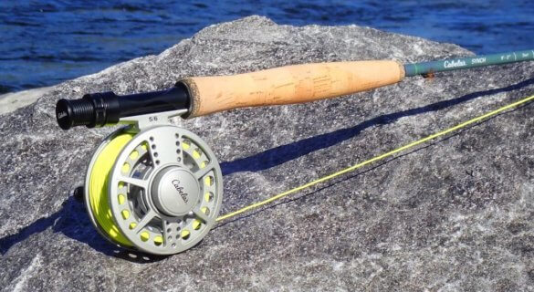 This photo shows the Cabela's Synch Fly Combo rod, reel, and fly line on a rock near a river.