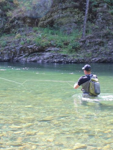 This image shows a fly fisher wading in a river while fishing with a fly rod and reel combo.