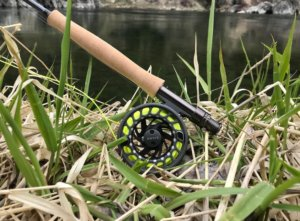This photo shows the new Orvis Clearwater fly rod and reel combo with the fly line, backing and a leader on the bank of a river.