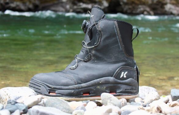 This wading boots photo shows the Korkers Devil's Canyon wading boot near a river.