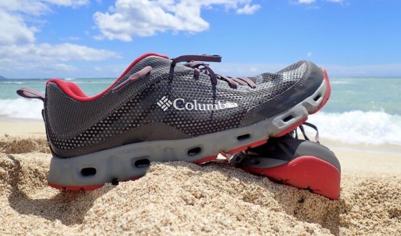 This photo shows the men's Columbia Drainmaker IV water shoe on a sandy ocean beach.