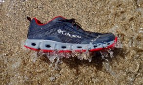 This photo shows the Columbia Drainmaker IV water shoe on beach getting hit by a small wave.